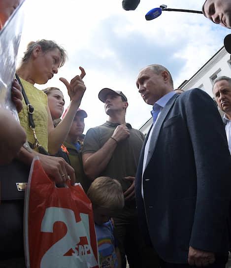 19 июля, Иркутская область. Президент России Владимир Путин и зампред правительства РФ Виталий Мутко (справа) во время встречи с жителями затопленных во время паводка населенных пунктов
