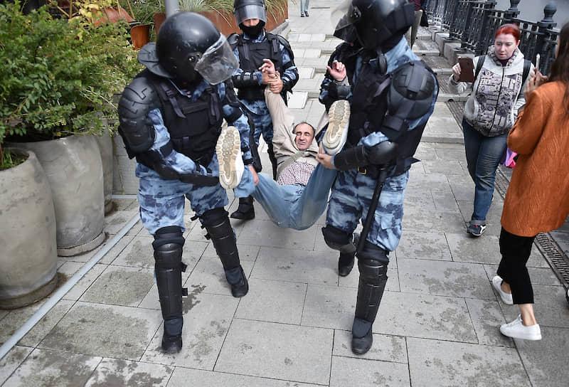 В поток людей то и дело вклинивались омоновцы, выхватывали кого-нибудь или обыскивали