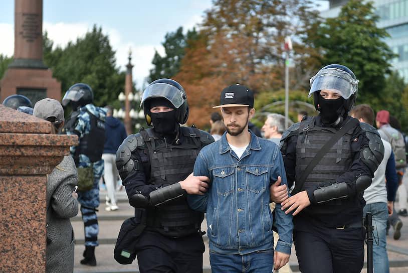На фото: участник несогласованной акции протеста в сопровождении ОМОНа