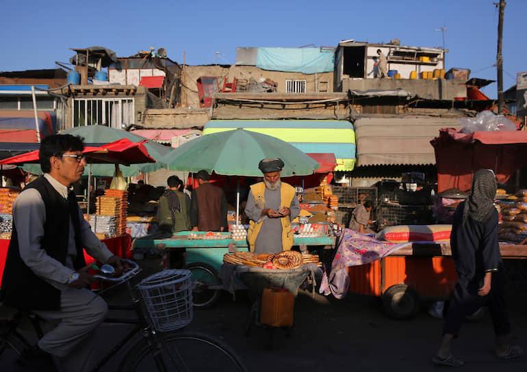 Кабул, Афганистан. Придорожный продавец хлеба считает деньги, ожидая клиентов на рынке