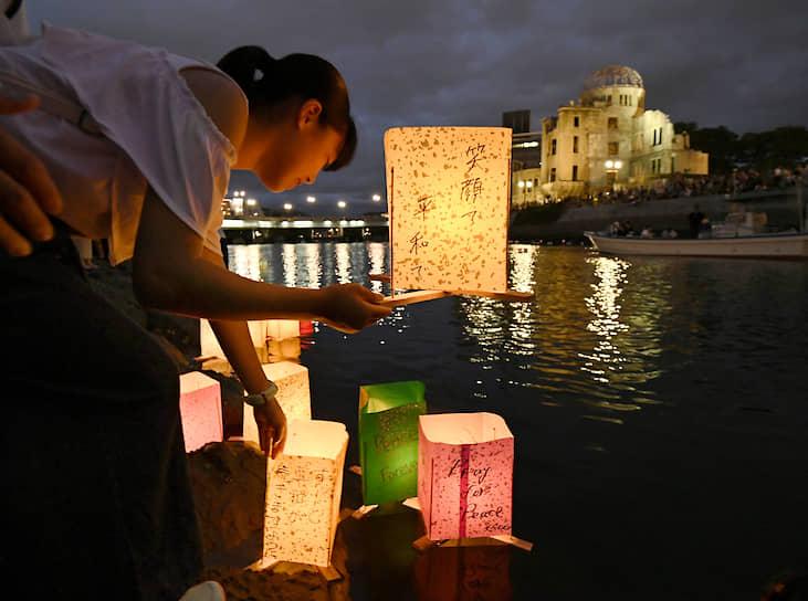 Хиросима, Япония. Девушка запускает бумажные фонарики на реке в память о жертвах атомной бомбардировки 6 августа 1945 года