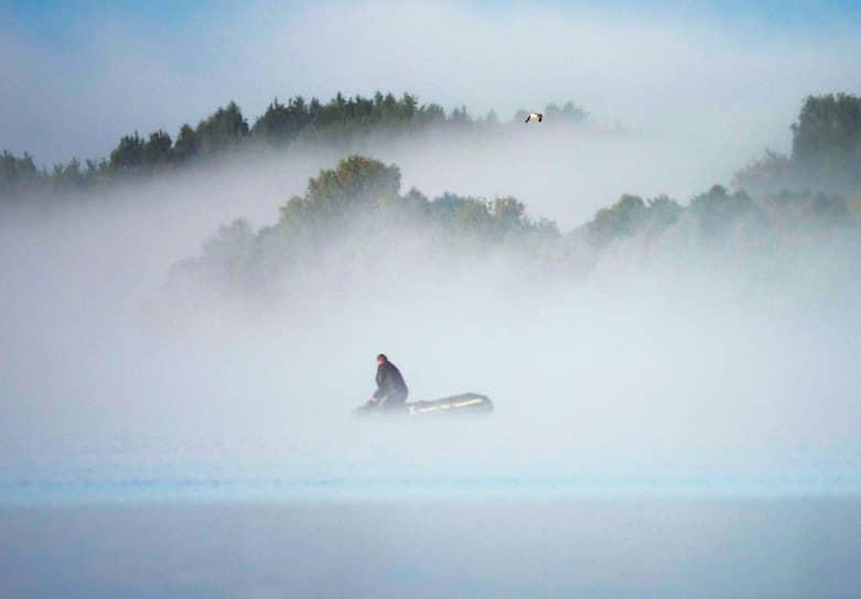 Калязин, Тверская область, Россия. Мужчина закидывает в Волгу рыболовную сеть