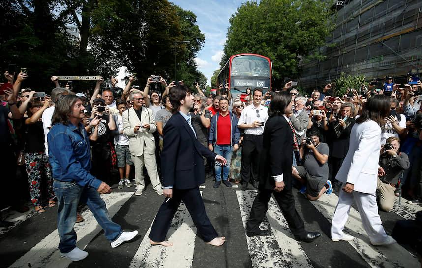 Лондон, Великобритания. Прохожие фотографируют, как участники кавер-группы The Beatles переходят дорогу по пешеходному переходу на Эбби-Роуд