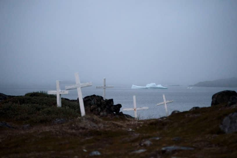 Кулусук, Гренландия. Кладбище на фоне плавающего в океане айсберга