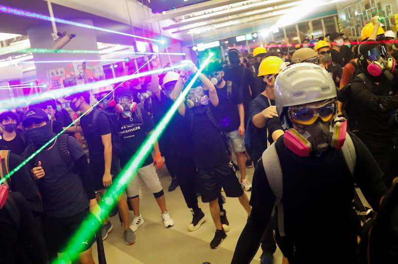 Гонконг. Протестующие в метро под лазерами, нейтрализующими полицейские камеры наблюдения