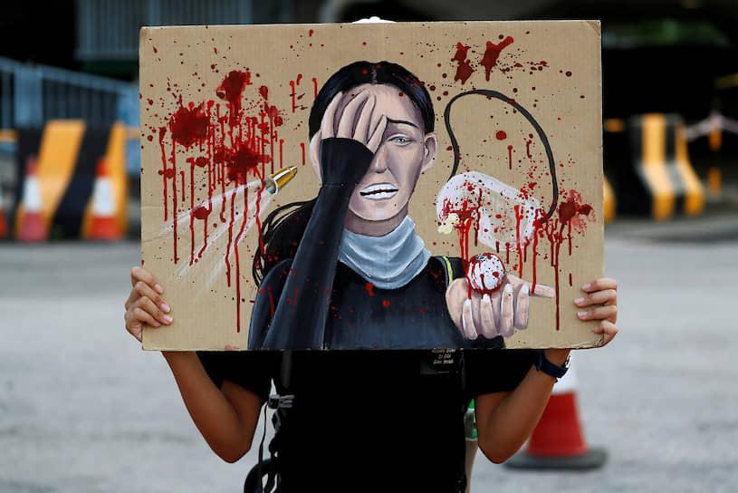 Гонконг, Китай. Студентка держит плакат с изображением женщины, которой во время акций протеста выстрелили в глаз