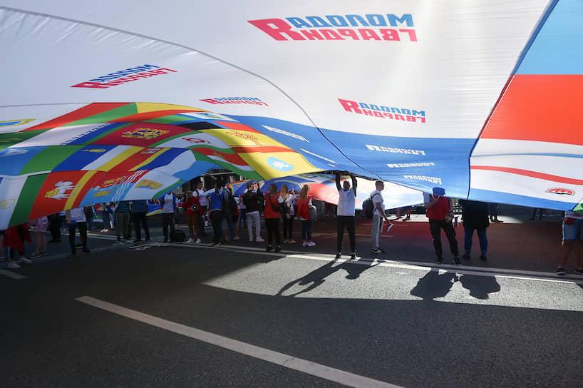 Участники флешмоба «Флаг-рекордсмен» на проспекте Сахарова