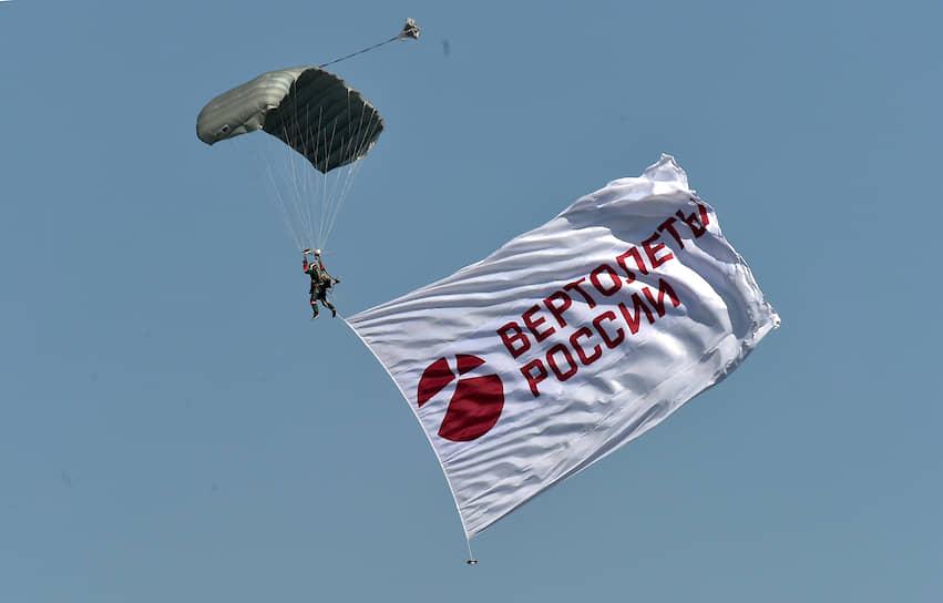 Парашютист с флагом компании «Вертолеты России» во время прыжка