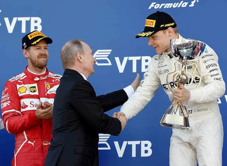 12 октября 2014 года Владимир Путин <b>посетил первый в истории Гран-при России «Формулы-1» в Сочи</b> и вручил приз победителю — пилоту «Мерседеса» Льюису Хэмилтону. С тех пор президент — постоянный гость этих соревнований<br> На фото: Владимир Путин награждает пилота «Феррари» Себастьяна Феттеля в 2017 году