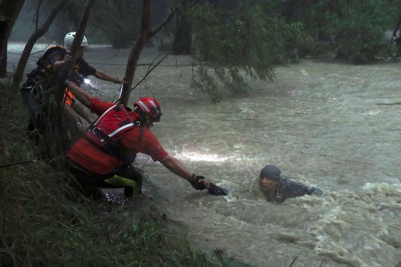 Гваделупа, Мексика. Спасатели вытаскивают из реки мужчину во время тропического шторма