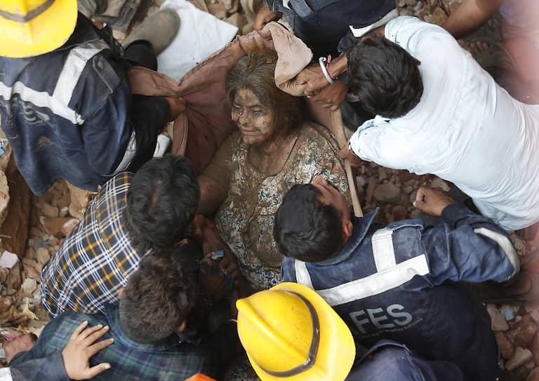 Ахмадабад, Индия. Спасатели с женщиной, вытащенной из-под завалов обрушившегося здания