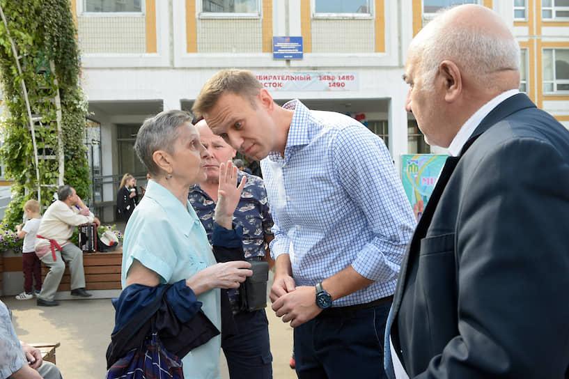 Основатель Фонда борьбы с коррупцией Алексей Навальный (в центре) после голосования на избирательном участке в школе №1043