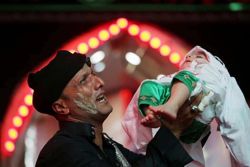 Кербела, Ирак. Мусульманин-шиит держит на руках ребенка во время религиозного траурного шествия