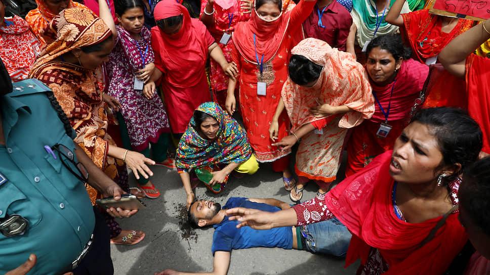Дакка, Бангладеш. Рабочий, раненный во время столкновений с полицией на акции протеста