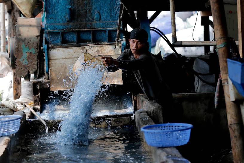 Джакарта, Индонезия. Рабочий на пункте по утилизации пластиковых отходов