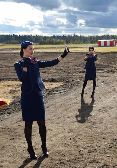 Аэропорт Шереметьево, Москва. Стюардессы фотографируются на новой взлетно-посадочной полосе во время церемонии ее открытия