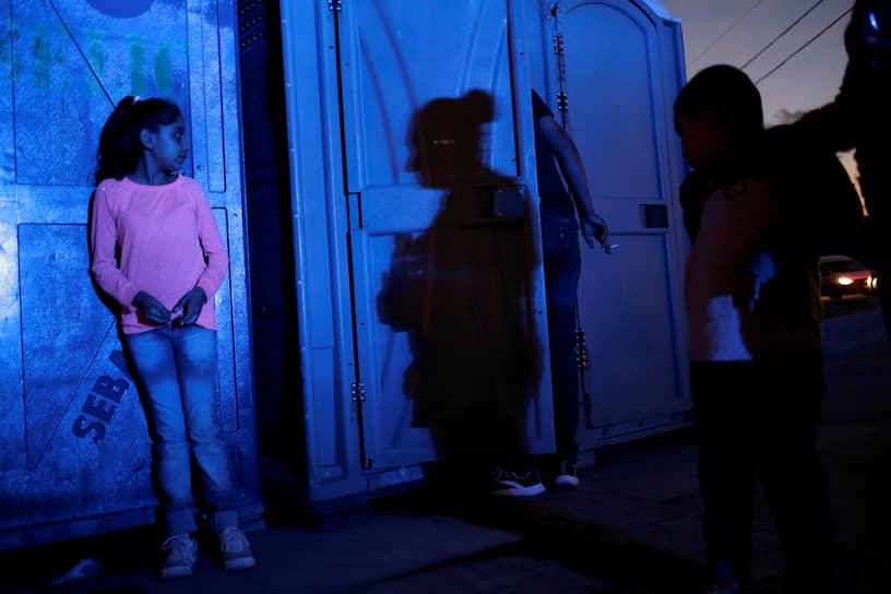 Сьюдад-Хуарес, Мексика. Юная мексиканка рядом с туалетами у погранперехода в США