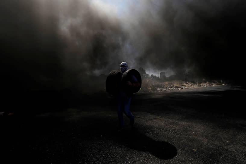 Бейт-Эль, Западный берег реки Иордан. Палестинец несет шины, чтобы сжечь их на акции протеста
