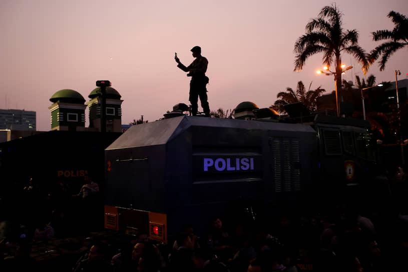 Джакарта, Индонезия. Полицейский держит в руках телефон во время акции протеста студентов у здания парламента