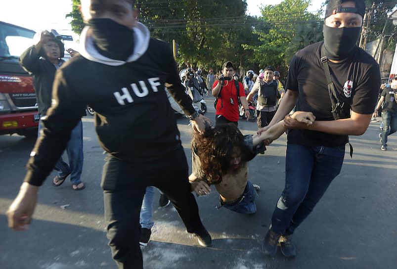 Макасар, Индонезия. Полицейские в штатском задерживают протестующих студентов
