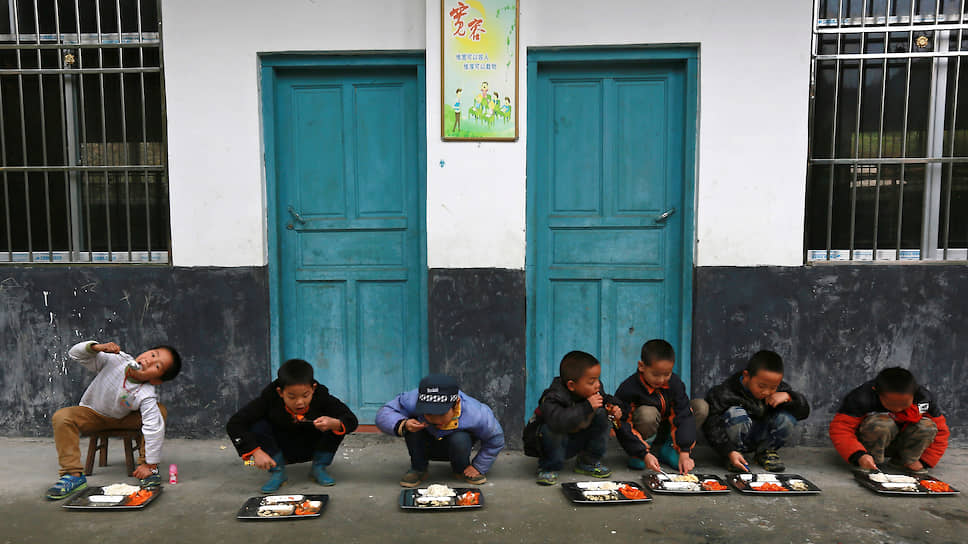 Ученики обедают возле здания школы, город Дунгуань