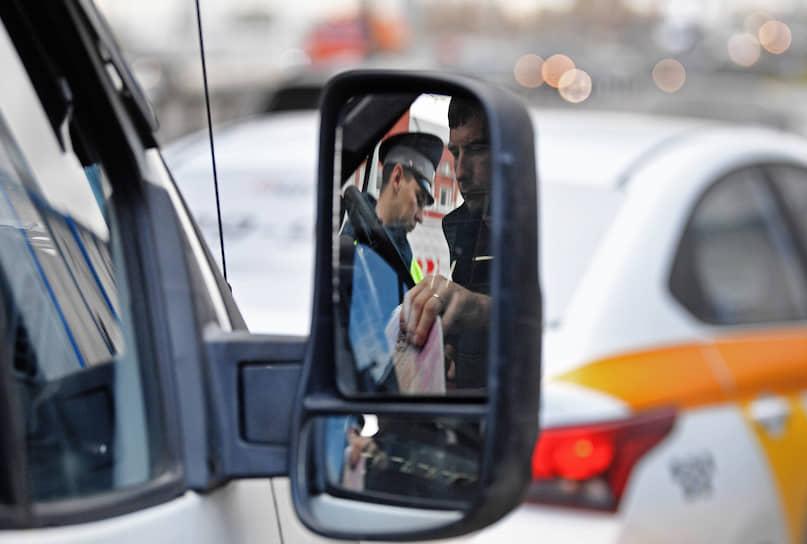 Москва. Сотрудник ГИБДД проверяет документы у водителя такси