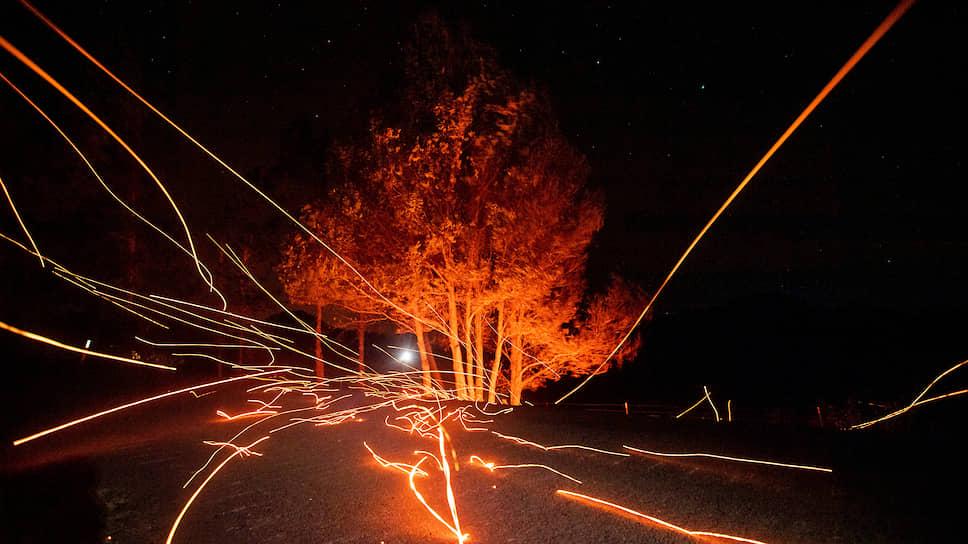 Калистога, США. Угли от пожара из-за сильного ветра летят над дорогой в Калифорнии