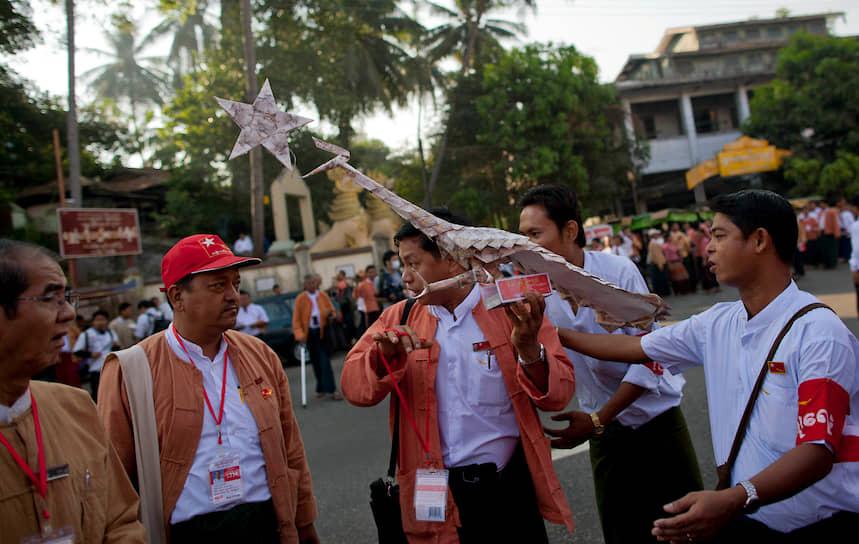 Зеленый павлин, называемый на бирманском языке даунг или у-дунг, является одним из национальных животных Мьянмы. Желтый боевой павлин — символ «Национальной лиги за демократию» — политической партии, основанной 27 сентября 1988 года <br>На фото: сторонники партии с копией боевого павлина, сделанного из банкнот, во время первого в истории конгресса партии в Янгоне (Мьянма), март 2013 года