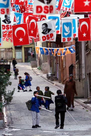 Символом «Демократической левой партии» Турции является голубь. Он же изображен на логотипе партии. ДПЛ выступает за создание в стране подлинной демократии, против чрезмерной социальной поляризации общества, и поддерживает национальное единство <br>На фото: жители Стамбула под турецкими флагами, эмблемами партии и фотографиями бывшего премьер-министра и лидера ДСП Бюлента Эджевита