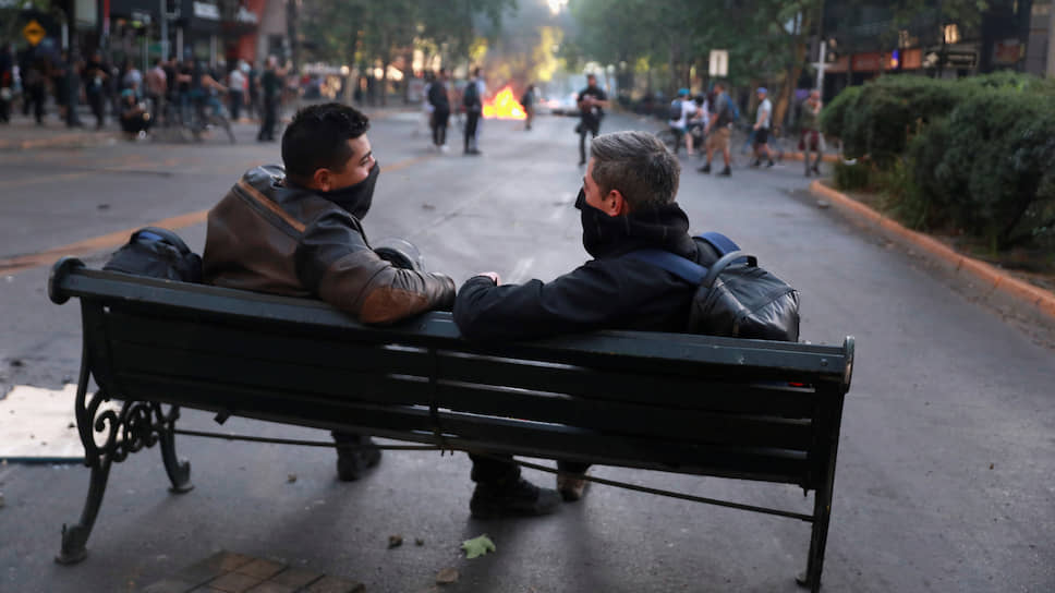 Сантьяго, Чили. Двое демонстрантов сидят на скамейке, пока происходят столкновения протестующих против правительства Чили с полицией