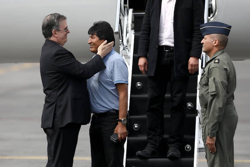 Эво Моралес (в центре) сначала заявлял о попытке госпереворота, потом убеждал сторонников, что не покинет президентский пост. Но в итоге он был вынужден покинуть страну и искать политического убежища в Мексике На фото: Эво Моралеса в аэропорту Мехико встречает министр иностранных дел Мексики Марсело Эбрард