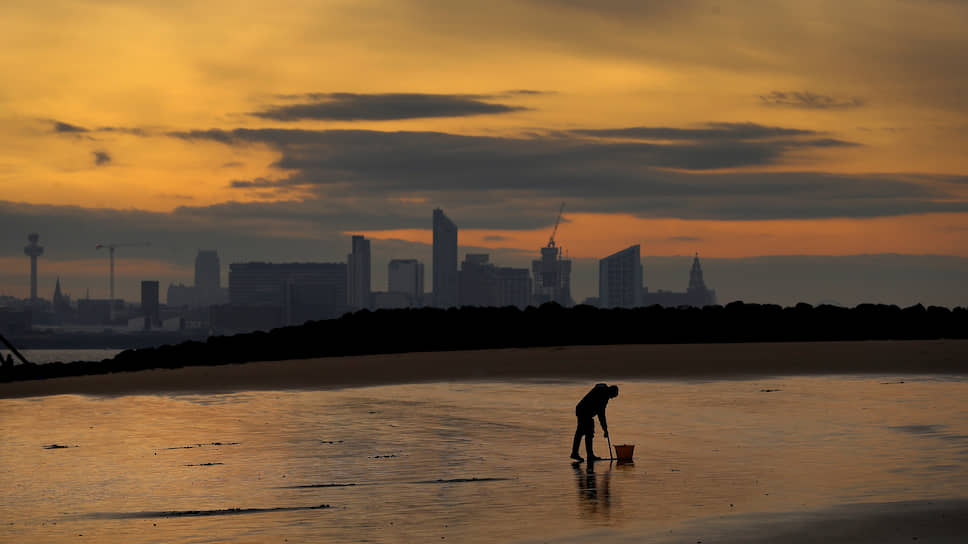 Ливерпуль, Великобритания. Рыбак ищет приманку на пляже