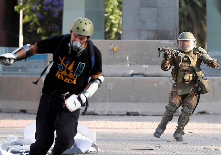 Сантьяго, Чили. Полицейский применяет слезоточивый газ против участника акции протеста