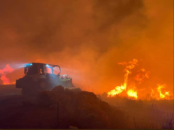 Штат Калифорния, США. Бульдозер на фоне лесного пожара