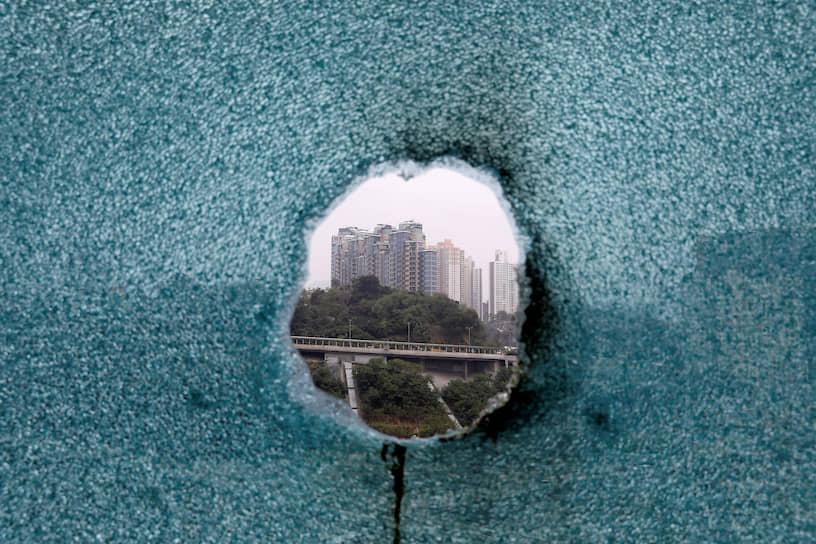 Гонконг, КНР. Вид на город из окна, простреленного во время операции по поиску протестующих