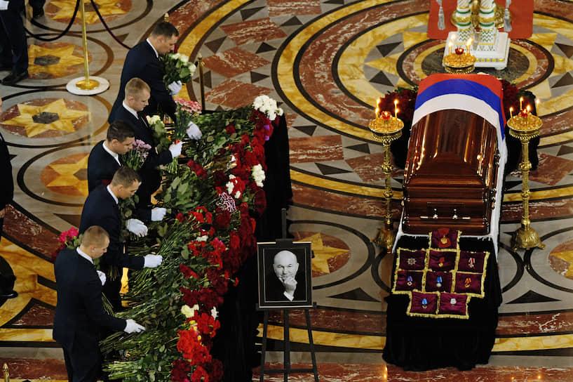 Закрытый гроб с покойным стоял по центру главного зала. Гроб был покрыт флагом России, за ним расставлены венки и цветы