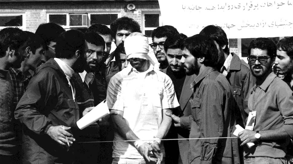 Иранские студенты показывают одного из заложников иностранным СМИ. Им было важно донести до международной общественности, почему они решились на захват посольства: «Мы верили, что имеем на это право – что, если мы не нападем на посольство, они могут напасть на нас». (11 ноября 1979 года)