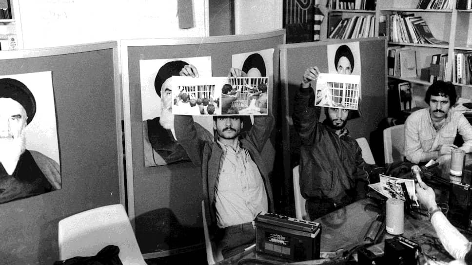 Один из главных организаторов захвата посольства Эбрахим Асгарзаде (слева) вместе с другими студентами показывает журналистам фотографии, сделанные в здании дипмиссии