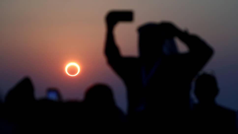 Эль-Хуфуф, Саудовская Аравия. Люди фотографируют кольцеобразное солнечное затмение