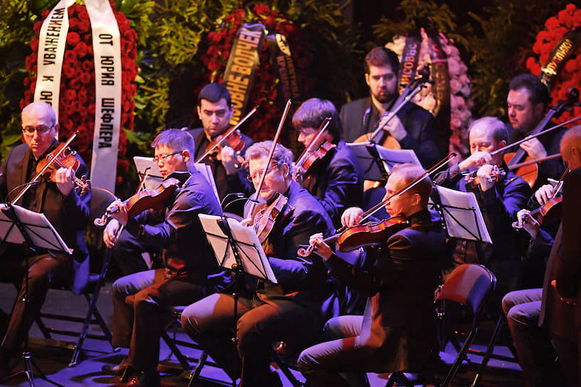 По левую сторону от гроба сидели музыканты — скрипичная секция оркестра. Под их музыку на заднике сцены сменялись фотографии и короткие видеозаписи с Галиной Волчек