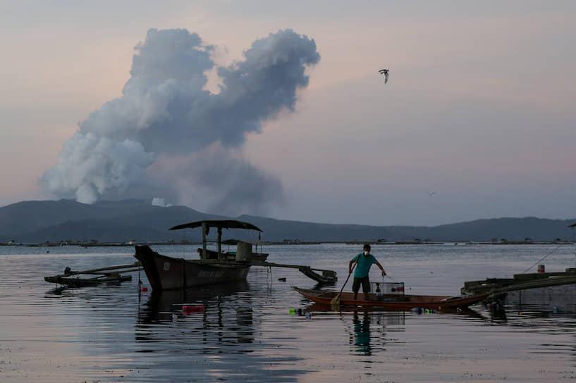 Талисай, Филиппины. Мужчина ловит рыбу во время извержения вулкана