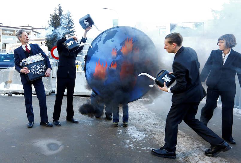 Участники акции протеста в Давосе поджигают глобус