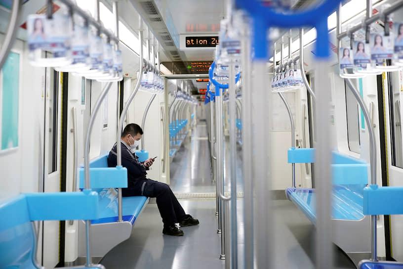 Жители крупных китайских городов избегают мест массового скопления людей<br> На фото: пассажир в метро Шанхая