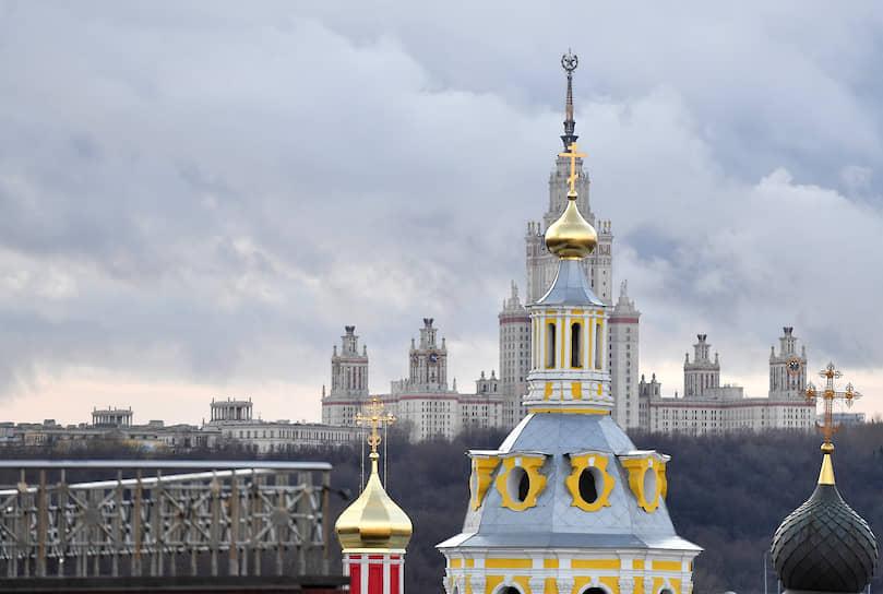 Москва, Россия. Купола Андреевского монастыря в Пленницах на фоне главного здания Московского государственного университета