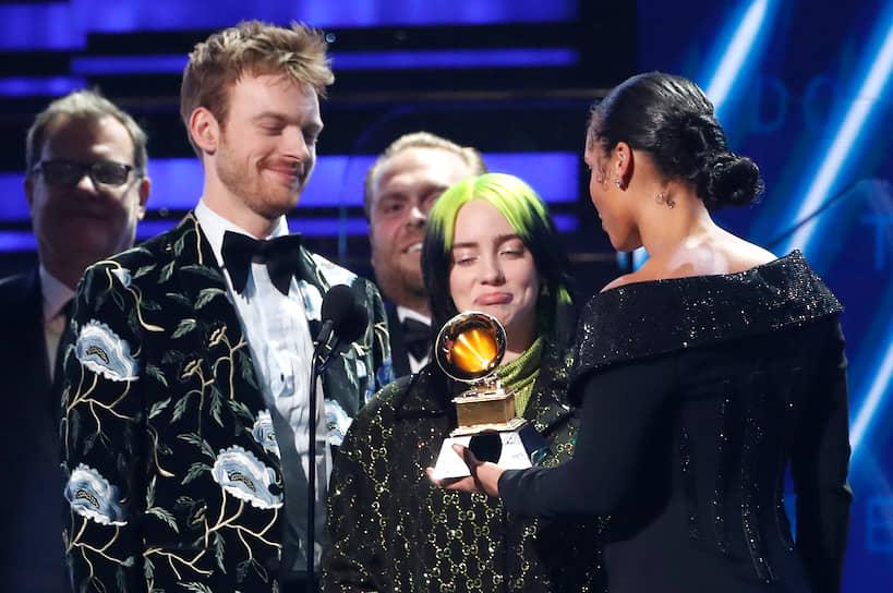 Ведущая Алиша Киз (справа) вручает награду в номинации «Лучший альбом года» певице Билли Айлиш и ее брату, продюсеру Финнеасу О'Коннеллу