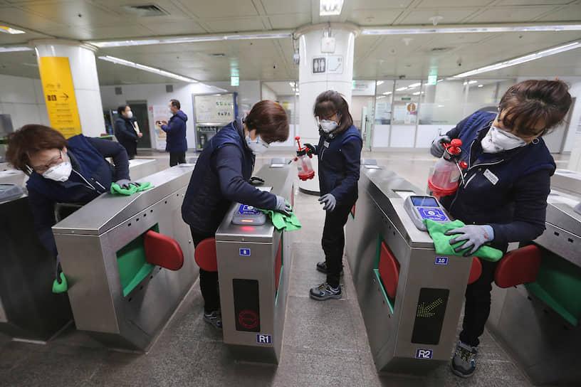 Сеул, Южная Корея. Работницы метрополитена проводят дезинфекцию турникетов, чтобы не допустить распространение коронавируса