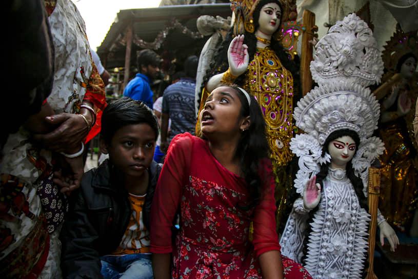 Калькутта, Индия. Дети сидят рядом со статуэтками, изображающими богиню мудрости Сарасвати