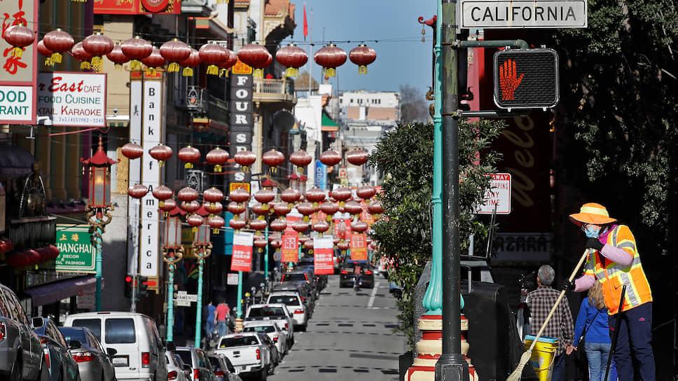 Уборщик в маске подметают улицу в районе Чайна-таун в Сан-Франциско, США