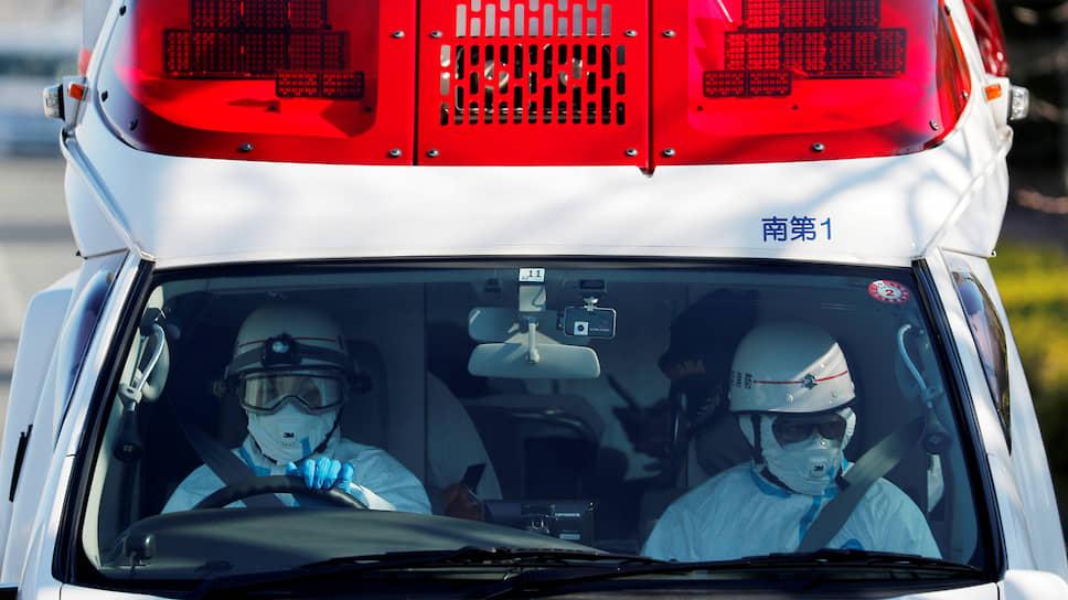 Работники скорой помощи в защитных костюмах предположительно везут в больницу человека с карантинного лайнера Diamond Princess (юг Токио, Япония)