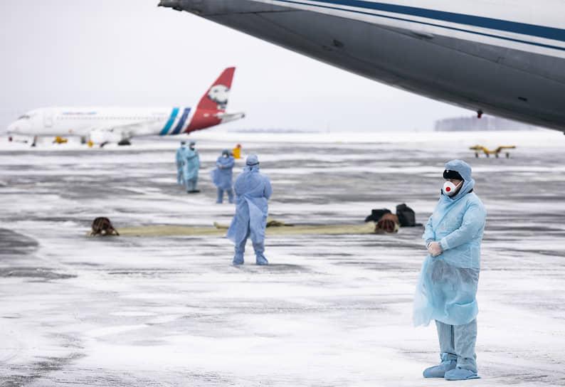 Тюмень, Россия. Сотрудники аэропорта во время встречи пассажиров из Китая